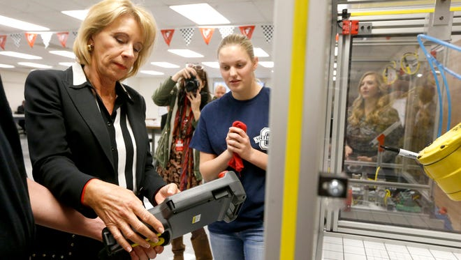 U.S. Secretary of Education Betsy DeVos is shown how to use a training robot during her tour of Oakland High School's mechatronics program in Murfreesboro on Wednesday, Nov. 29, 2017. Oakland senior Sara Carmichael stands in the background to help.