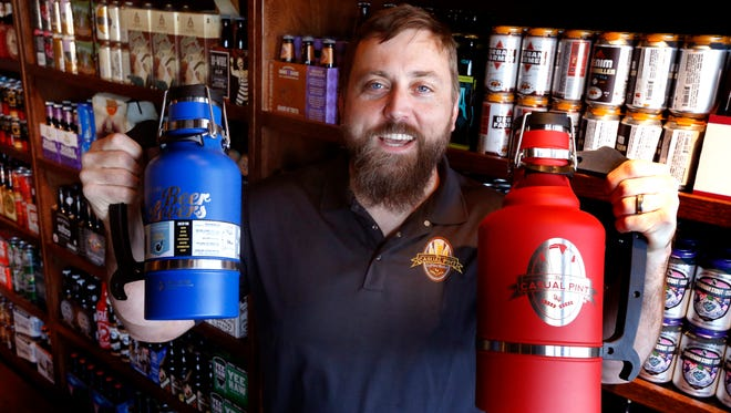 Chris Norris the owner of the new beer bar in Smyrna The Casual Pint shows off the aluminum growlers called the drink tanks, on Wednesday, Dec. 13, 2017 at his store.