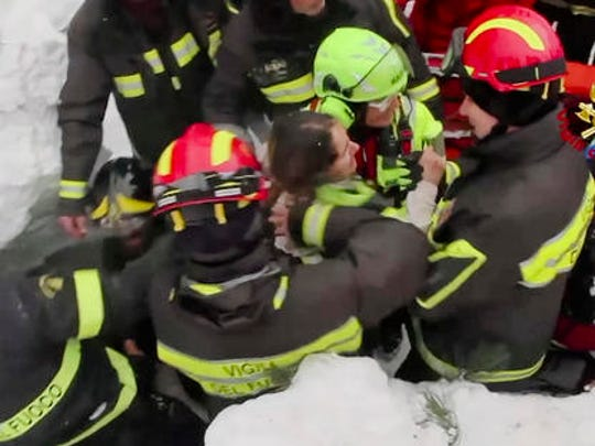 This frame from video shows Italian firefighters extracting a woman alive from under snow and debris of an hotel that was hit by an avalanche on Wednesday, in Rigopiano, central Italy, Friday, Jan. 20, 2017.