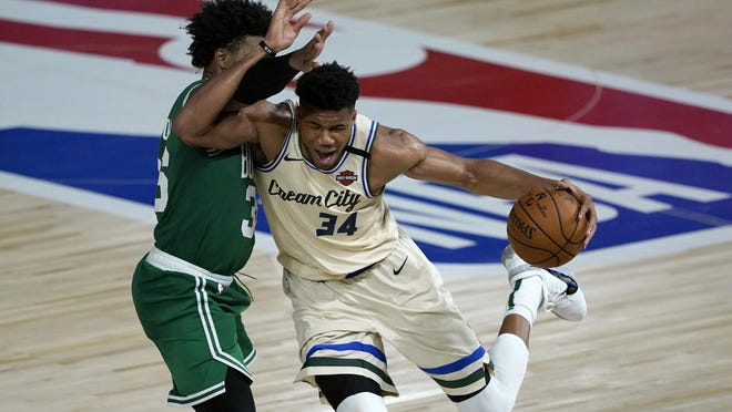 The Milwaukee Bucks' Giannis Antetokounmpo drives against the Celtics' Marcus Smart during the second half Friday night in Lake Buena Vista, Fla.