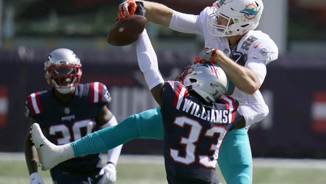 New England Patriots cornerback Joejuan Williams (33) breaks up a pass intended for Miami Dolphins tight end Mike Gesicki (88) in the second half of an NFL football game, Sunday, Sept. 13, 2020, in Foxborough, Mass.