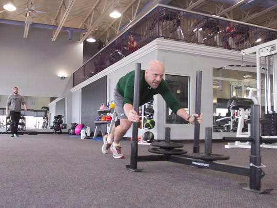 2 Studio Gym client Russ Chambers performs a sled push