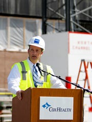 President and CEO of CoxHealth Steve Edwards speaks at a ceremony commemorating the topping out of the new Cox Medical Center South Patient Tower is hoisted into place by a tower crane on Thursday, Sept. 25, 2014