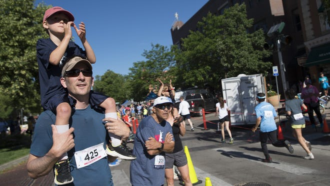 Mason Wiebe and his son, Hank, 5, cheer on fellow runners as they cross the finish line during the Father's Day 5K in Old Town on Sunday, June 18, 2017.
