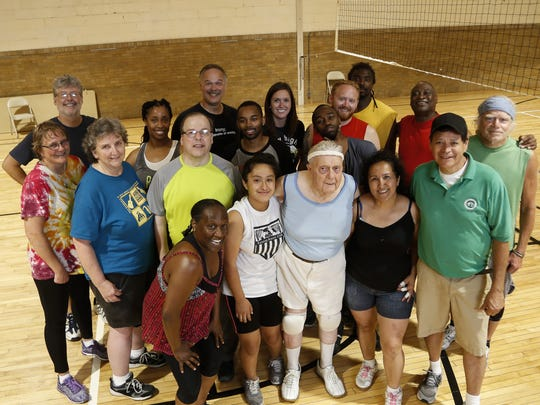 Members of the the Lansing Park and Recreation's volleyball league, gather around oldest member Robert Luscombe (blue tank top, middle).  The group plays on Tuesday evenings at Foster Community Center in Lansing.  The age range is diverse - The youngest player is 12, the oldest is 84.