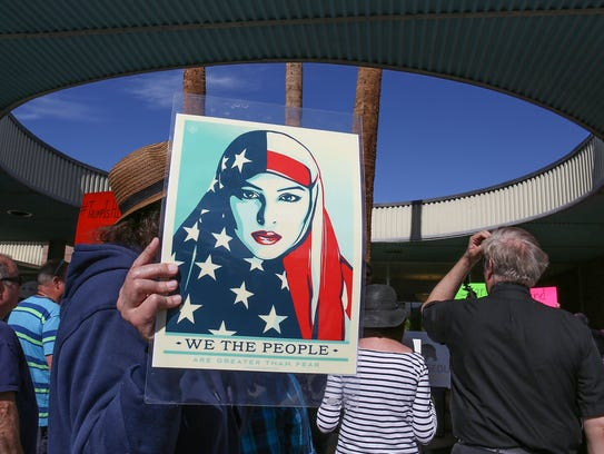 A man holds a poster of a woman wearing an American