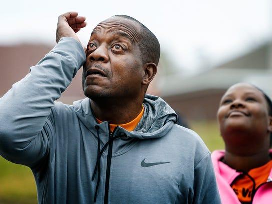 Reginald Johnson (left) wipes away tears after releasing