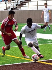 Roger Bacon's Gideon Fomba (9) dribbles past Mt. Healthy's