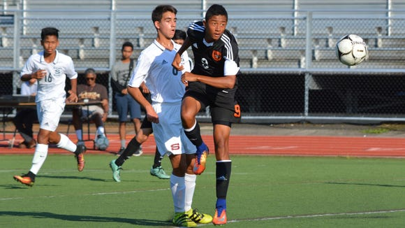 White Plains' Carl Fisher (9) keeps the ball moving