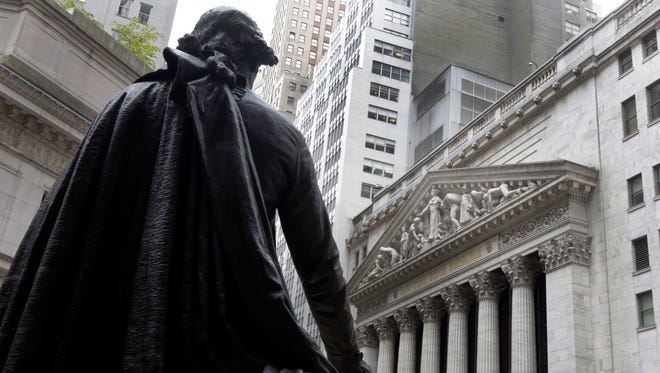 In this Oct. 2, 2014, file photo, the statue of George Washington on the steps of Federal Hall faces the facade of the New York Stock Exchange.