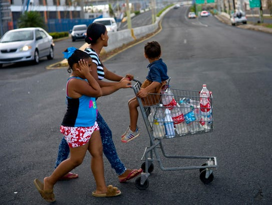 A resident collects water in Bayamon, Puerto Rico,