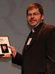 The Rev. Greg Bohren accepts his 20 Under Forty award in November 2014.