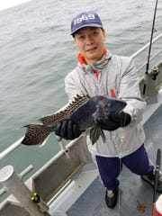 Wu Jain holds a 4-pound sea bass he caught on the Dauntless
