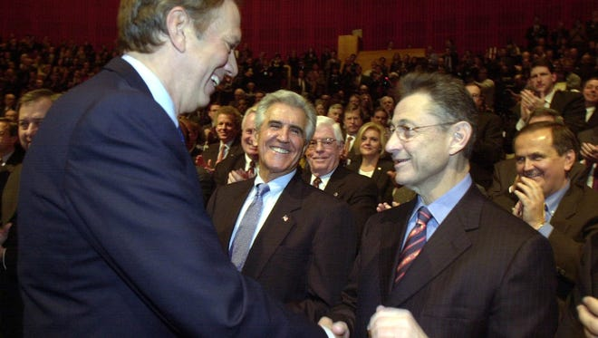 Governor George Pataki greets Senate majority leader Joseph Bruno, left, and Assembly Speaker Sheldon Silver before the budget address in Albany on January 29, 2003.