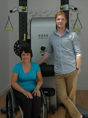 Ryan Eber (right) and Rosemarie Rossetti in front of one of his fitness machines.