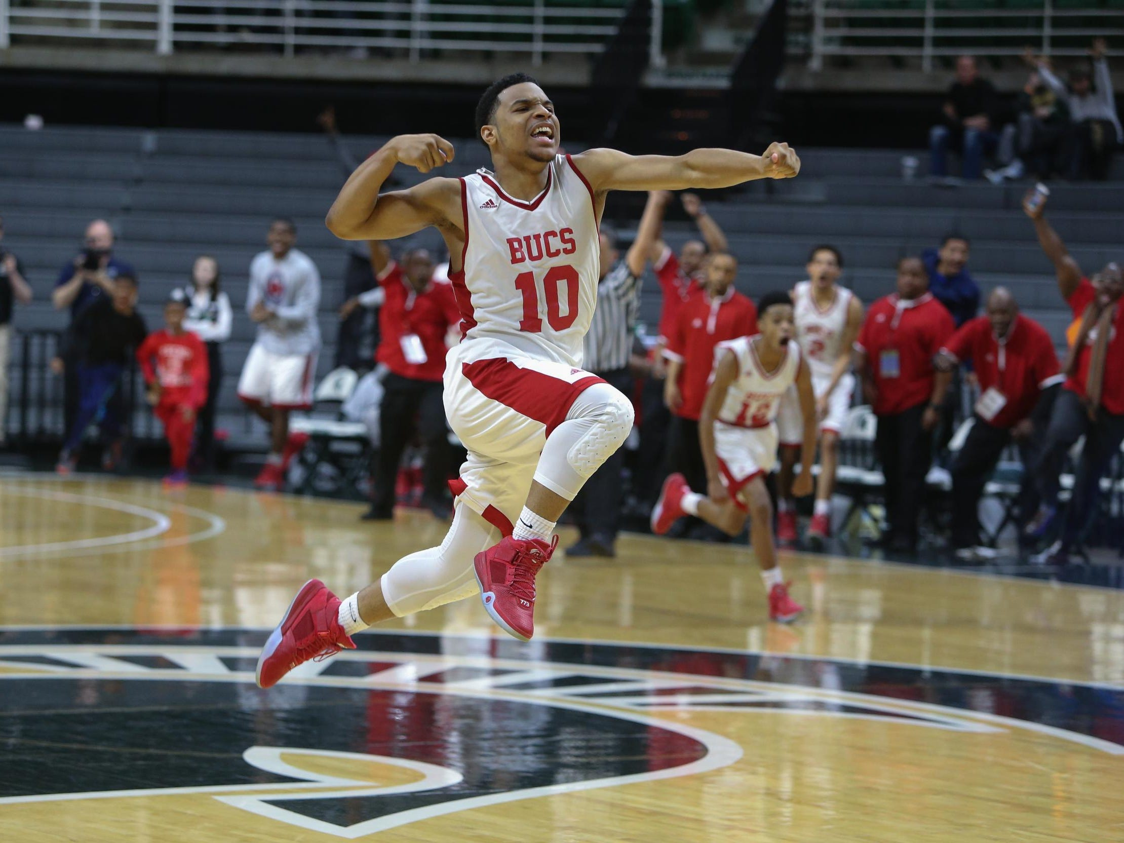 Flint Beecher high schools Malik Ellison celebrates after hitting the game winner against Detroit Loyola high schools Keith Johnson during fourth period action in the State Class C semifinal on Thursday, March 24,2016 at Breslin Center in East Lansing. Kirthmon F. Dozier/Detroit Free Press