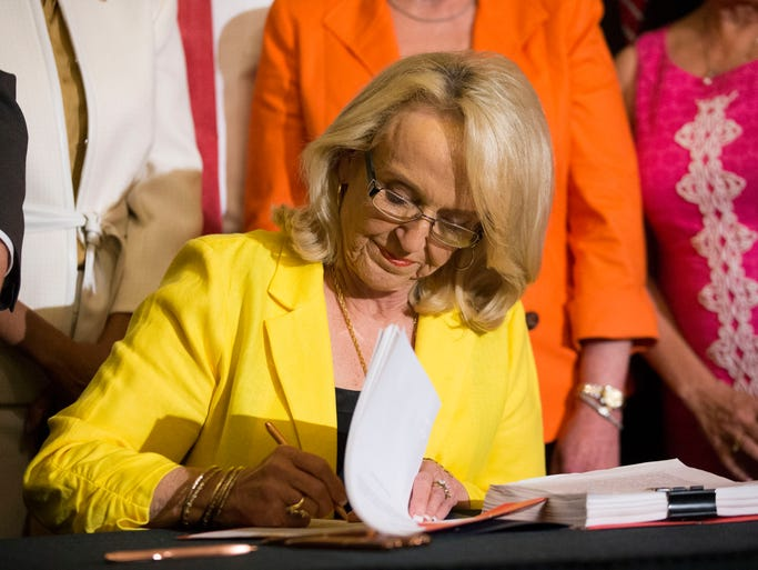 Arizona Gov. Jan Brewer signs into law Senate Bill 1002 which provides about $60 million in additional funding to cover the cost of adding more than 160 new staff, from caseworkers to police investigators to the new Department of Child Safety during the signing ceremony on May 29, 2014, at the state Capitol in Phoenix.