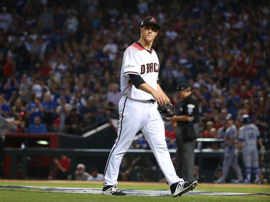 Zack Greinke walks off the field after being pulled in the sixth inning of Monday's season-ending loss.