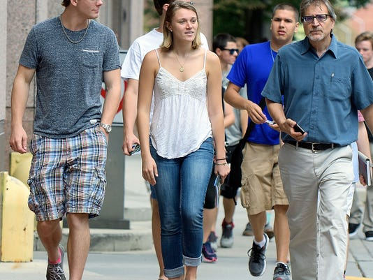 York College freshmen Nick Vandermark of West Chester, Chester County, and Miranda Gajda of Lewisburg, Union County, walk along South George Street  Thursday with Dominic DelliCarpini, the school's dean of academic affairs and head of the Center for Community Engagement. The students and other Graham Scholar recipients were given a tour of downtown.