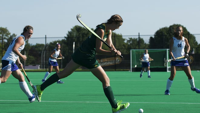 Vermont's Lauren Tucker (21) hits the ball down the field during the women's field hockey game between the Holy Cross Crusaders and the Vermont Catamounts at Moulton Winder Field on Wednesday afternoon in Burlington.