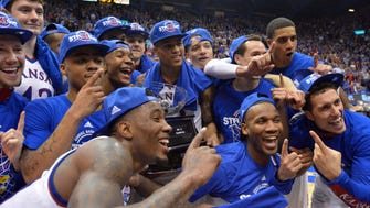 The Kansas Jayhawks players celebrate with the championship trophy after the game against the West Virginia Mountaineers at Allen Fieldhouse. Kansas won their 11th consecutive Big 12 Championship 76-69.
