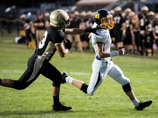Littlestown quarterback Jakob Lane avoids a tackle from Delone Catholic's Jon Pierce during play on Friday, Sept. 29, 2017. The Bolts defeated the Squires 28-27.