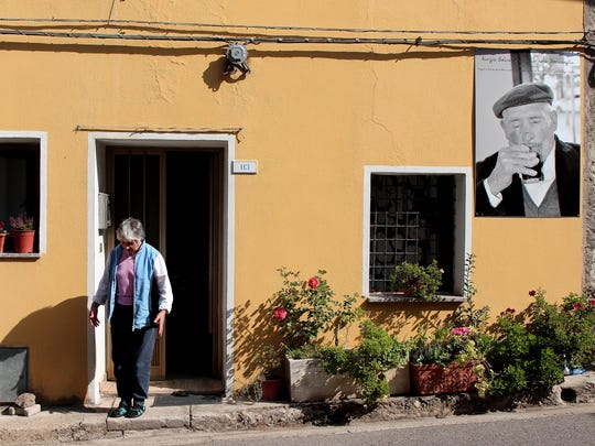 A resident of Seulo, Italy, leaves a home that is adorned