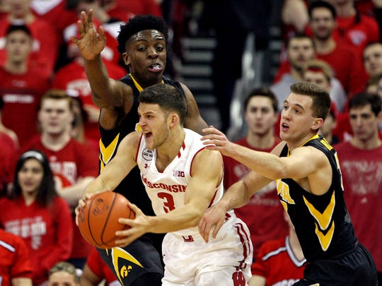 Mar 2, 2017; Madison, WI, USA; Wisconsin Badgers guard Zak Showalter (3) attempts to pass as Iowa Hawkeyes forward Tyler Cook (top) and guard Jordan Bohannon (3) defend at the Kohl Center.