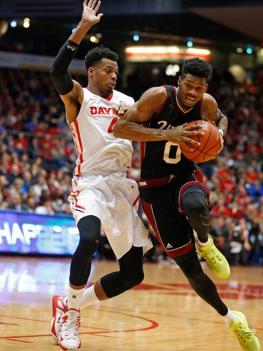 Massachusetts guard Donte Clark (0) drives to the basket in front of Dayton's Charles Cooke during the first half of an NCAA college basketball game Wednesday, Jan. 6, 2016, in Dayton, Ohio.  (AP Photo/Gary Landers)