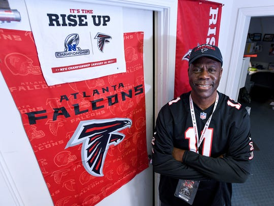 Long time Atlanta Falcons fan George Turmon poses with some of his Falcons gear at his office in Greenville on Thursday, Feburary 2, 2017.