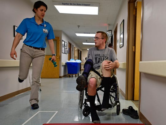 Mark Frahn practices walking with the help of physical therapy student Alayna Kalinay at HealthSouth Rehabilitation Hospital of York on Thursday, March 1, 2018. Frahn fractured his L1 vertebrae after crashing his dirt bike on June 11. Doctors told him he wouldn't be able to walk again.