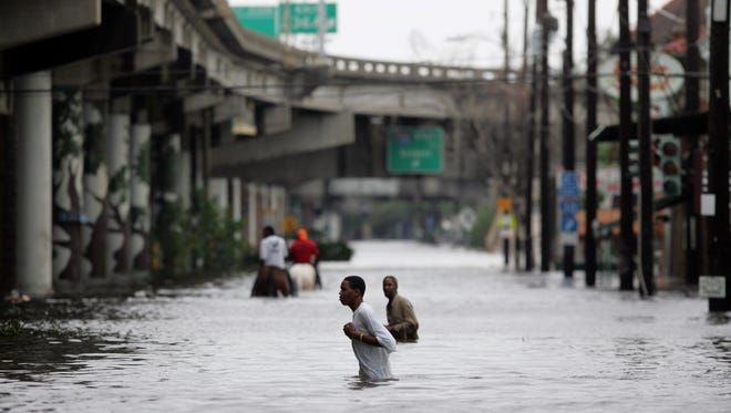 New Orleans residents walk through chest deep floodwater after Hurricane Katrina made landfall on Aug.29, 2005.