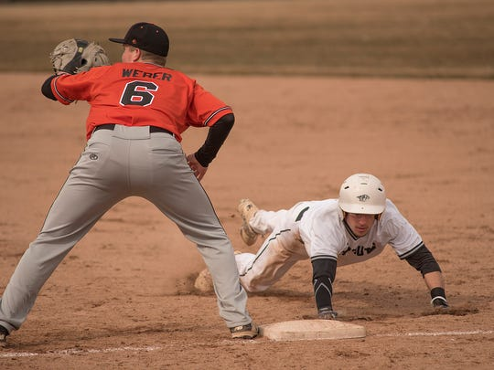 Northville first baseman Matt Weber (6) reaches for the pick-off throw while Plymouth's Kyle Aniol (9) dives back into the bag.