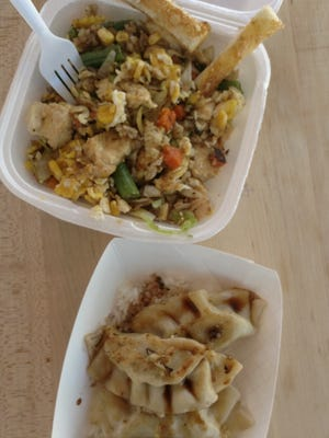 The fried rice bowl ($7) with mixed vegetables, egg and chicken. Pictured below are the dumplings, served on a bed of rice with soy sauce ($6) at Happy Dog food truck.