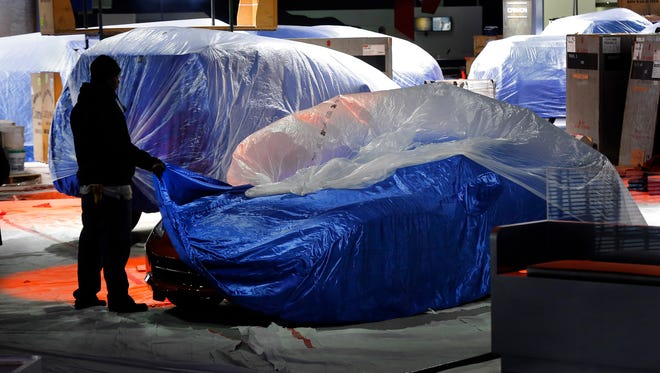 A worker with a covered  Chevrolet Corvette Stingray during set up for the Detroit Auto show, which opens to the media Monday.