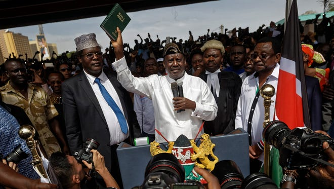 """Opposition leader Raila Odinga holds a bible aloft after swearing an oath during a mock """"swearing-in"""" ceremony at Uhuru Park in downtown Nairobi, Kenya Tuesday, Jan. 30, 2018."""