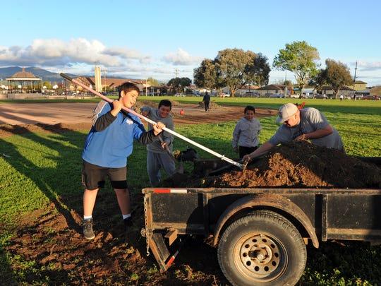 Volunteers at Closter Park in east Salinas help spread topsoil on sunken spots in a LIttle League field.