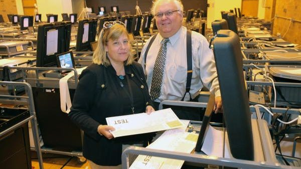 Rockland County Commissioners of Elections Kristen Stavisky and Louis Babcock  stand among dozens of voting machines being prepped at the Yeager Health Center campus in Ramapo Aug. 19, 2014.