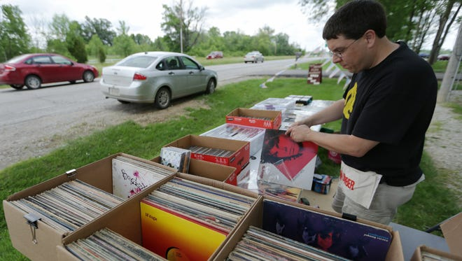 Scott Burress takes a look at records he's selling at his booth outside Gilley's Antique Mall in Plainfield, on Friday, May 29, 2015. The annual event, which runs through Sunday, stretches along the historic road from Maryland to Missouri.