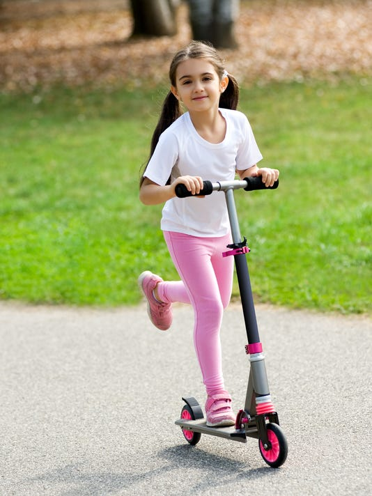 Cute young girl playing on a scooter