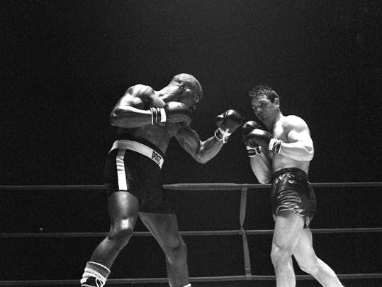"""FILE - In this Feb. 23, 1965 file photo, Rubin """"Hurricane"""" Carter, left, knocks out Italian boxer Fabio Bettini in the 10th and last round of their fight at the Falais Des Sports in Paris. Carter, who spent almost 20 years in jail after twice being convicted of a triple murder he denied committing, died at his home in Toronto, Sunday, April 20, 2014, according to long-time friend and co-accused John Artis. He was 76. (AP Photo/File)"""