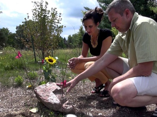 Dan and Michaela Cady visit the grave of their daughter Kennis, who took her life this summer at the age of 12. They brought a sunflower and sea shells to place at her headstone at White Haven Memorial Park in Pittsford.