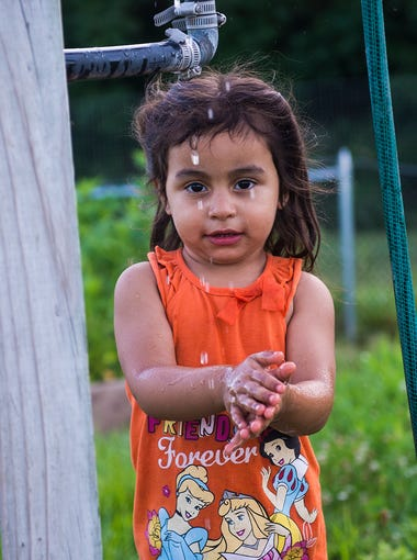 Deborah Vega, 3, washes her hands at one of the garden pumps during a Monday night session on July 11, 2016.