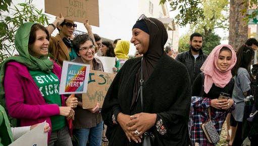 Shakera Healy, center, visits with supporters Susan Chopra, Lindsey Raney and Cathy Cramer as she arrives for prayers at the Nueces Mosque in Austin, Texas, Friday, Nov. 18, 2016. Dozens of people from various backgrounds and religions lined the sidewalks in front of the mosque to stand in solidarity with their Muslim neighbors and denounce prejudice and hate.