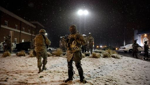 Snow falls as Missouri National Guard stand outside of the Ferguson Police Department Wednesday, Nov. 26, 2014, in Ferguson, Mo. A grand jury's decision not to indict Ferguson police officer , Darren Wilson, in the shooting death of Michael Brown has sparked protests nationwide, triggering debates over the relations between black communities and law enforcement.