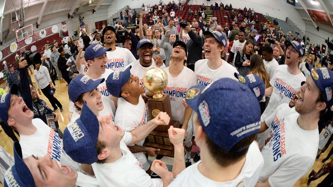 Colgate players celebrate with the championship trophy after an NCAA college basketball game against Bucknell for the championship of the Patriot League men's tournament in Hamilton, N.Y., Wednesday, March 13, 2019. Colgate won 94-80. (AP Photo/Adrian Kraus)