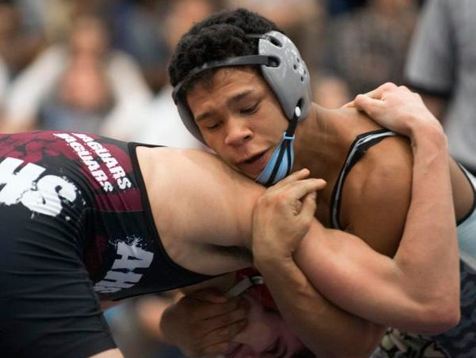 Cape Henlopen's Austin Smith, left, grabs the leg of Charter of Wilmington's Lameck Muaka during the DIAA Individual Wrestling State Tournament at Cape Henlopen on Friday.