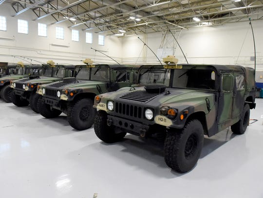 Several Humvees are parked in a row inside the Thomas
