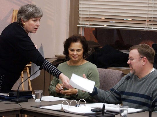 On Dec. 2, 2002, the Citizen Complaint Authority holds its first meeting. Nancy Minson, chairperson, passes out agenda information to board members Marta Camille Haamid and John Eby.