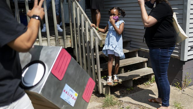"""Harvard Park first-grader Aaliyah Sanders smiles through her face mask as she gets her """"Smart Car"""" delivered to her home by her first-grade teacher Allison Acker, right, in preparation for remote learning during the COVID-19 pandemic, Wednesday, Aug. 26, 2020, in Springfield. The """"Smart Car"""" is made up of a U-Haul box that Acker made with headlights made from paper plates and includes a license plate with each students name. The boxes are intended for students to sit inside as a """"dedicated learning space"""" with their lap desks and iPads."""